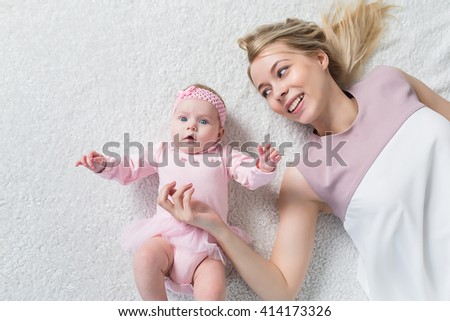 Young beautiful mother playing with her baby. motherhood concept, love and care. - stock photo