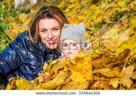 Young beautiful mother playing with her daughter, who is biting mother's nose, in the autumn park among the yellow fallen maple leaves, happy laughing emotional family