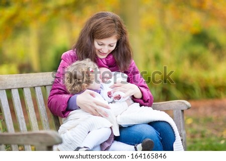 Young beautiful mother playing with her toddler daughter and newborn baby in an autumn park sitting on a bench under a warm knitted blanket - stock photo