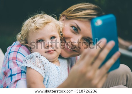 Young beautiful mother takes selfie with her daughter during a walk outdoors. Toned image - stock photo