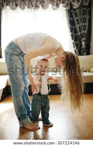 young beautiful mother teaches baby to walk - stock photo