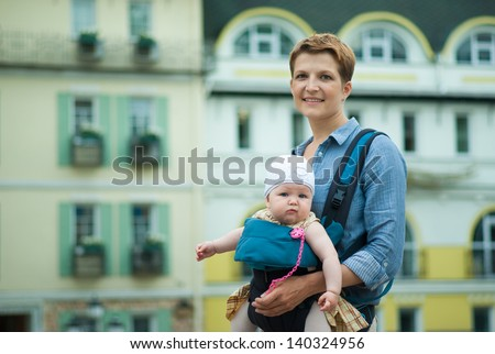 Young beautiful mother with a child walking around the city - stock photo