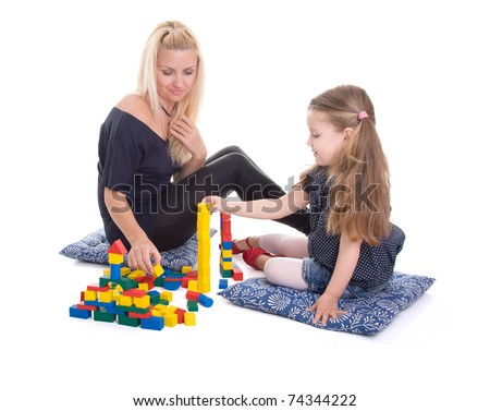 Young beautiful mother with a daughter playing cubes - stock photo