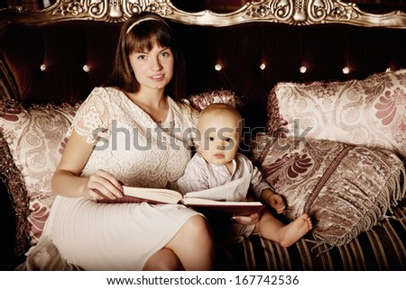 Young beautiful mother with a small child in the interior reading a book together. Smiling family in the bedroom reading a book. Mom and baby on the couch