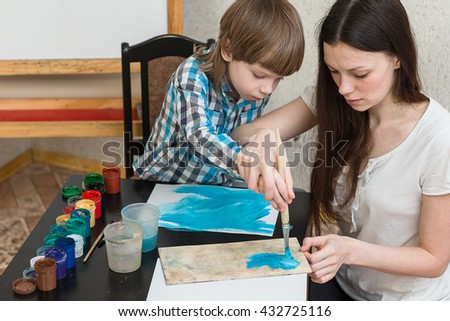 Young beautiful mother with boys son paint colors at home. Mom teaches son to paint colors. - stock photo