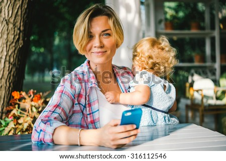Young beautiful mother with her toddler daughter in a street cafe - stock photo