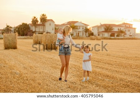 Young beautiful mother with her two children run and laugh at sunset and haystacks summer
