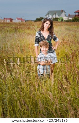 young beautiful mother with son having fun on the lawn with green grass - stock photo