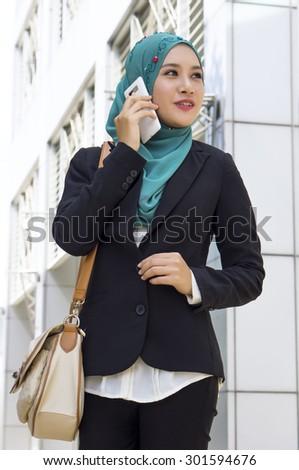 Young Beautiful Muslim business woman holding Smartphone  - stock photo