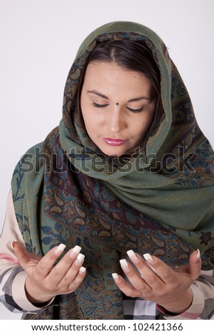 Young beautiful muslim woman with a scarf on her head praying.