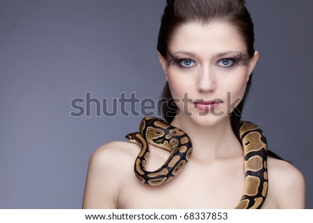 Young, beautiful, naked sensual woman with snake on her arms, portrait on light blue background, a lot of copyspace available