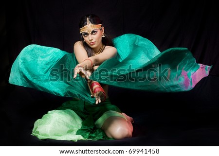 young beautiful oriental woman with a veil dancing over a dark background - stock photo