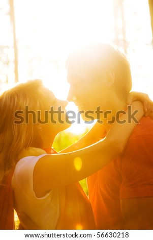 Young beautiful pair of lovers kissing at sunset - stock photo
