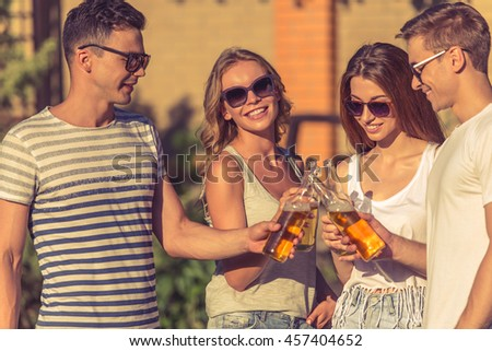 Young beautiful people in casual clothes and sun glasses are clinking bottles of beverage and smiling while resting outdoors. One girl is looking at camera - stock photo