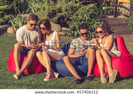Young beautiful people in casual clothes and sun glasses are using gadgets, talking and smiling, sitting on bean bag chairs while resting outdoors - stock photo
