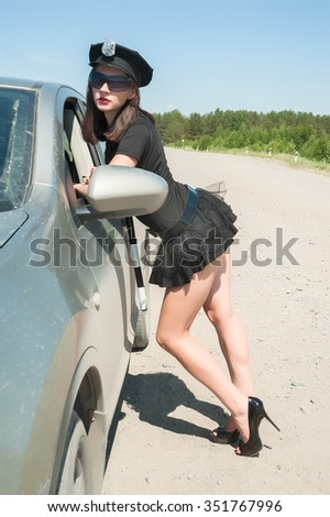 Young beautiful police woman stops car for checking driver license - stock photo