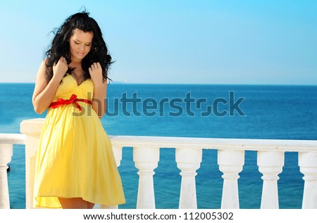 Young beautiful pregnant woman in dress over blue sky, ocean - stock photo