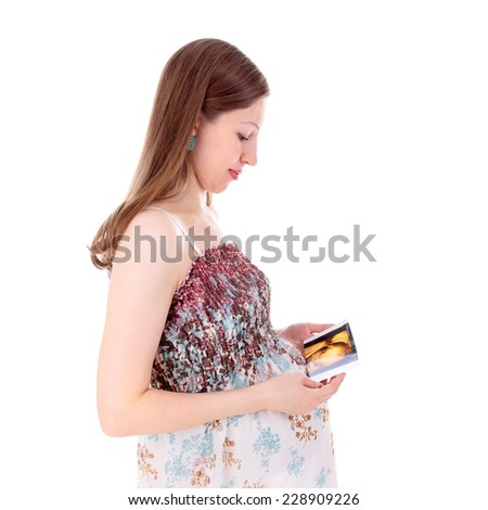 young beautiful pregnant woman looking at the baby ultrasound scan - stock photo