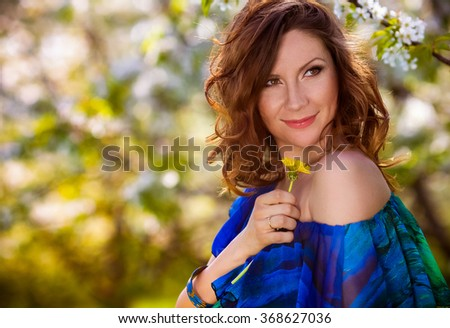 Young beautiful pregnant woman resting in spring garden - stock photo
