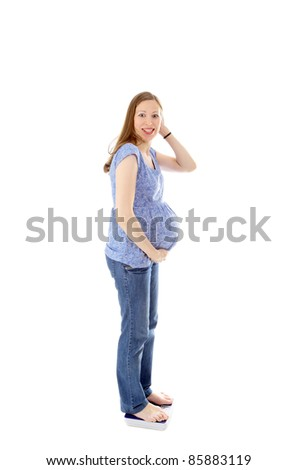 young beautiful pregnant woman shocked by her own weight - stock photo