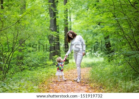 Young beautiful pregnant woman walking with her baby daughter in a golden autumn forest - stock photo