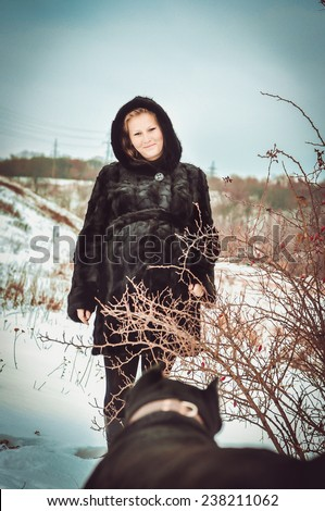 Young beautiful pregnant woman with cane corso dog outdoors - stock photo