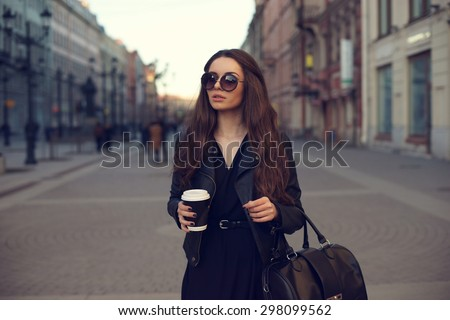 Young beautiful pretty girl walking along the street with handbag and cup of coffee. - stock photo
