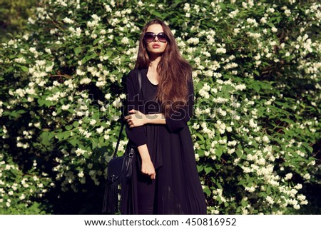Young beautiful pretty stylish girl in black blouse and sunglasses standing and posing against green bushes with white blooming flowers on a sunny summer day