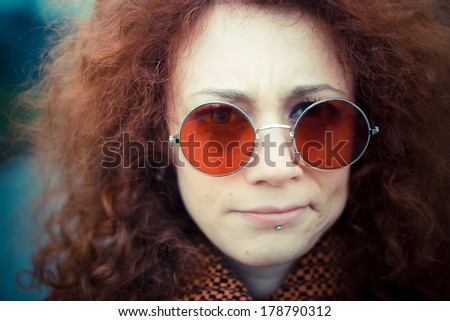 young beautiful red curly hair woman with sunglasses at the park