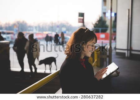 young beautiful red dressed vintage hipster woman in street town using tablet - stock photo