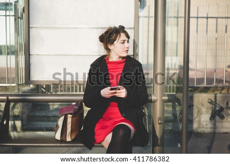 young beautiful red dressed vintage hipster woman sitting at the bus stop waiting, holding smart phone overlooking - commuter, technology concept - stock photo