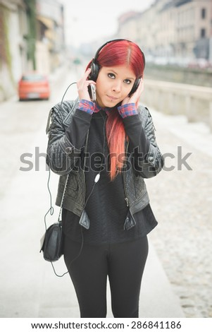 young beautiful red hair venezuelan woman lifestyle in the city of milan outdoor street listening music with headphones - stock photo