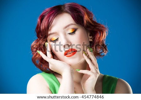 Young beautiful red-haired caucasian woman in green dress posing in studio on blue background, professional makeup and hairstyle, expressive portrait - stock photo