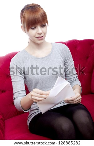 young beautiful red haired girl sit on red sofa and received a letter in front of white background - stock photo