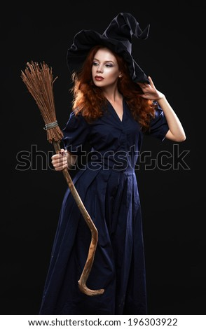 Young beautiful red-haired witch with a broom in the dark