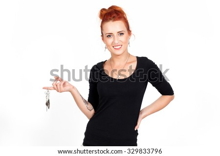 Young beautiful, red-haired woman, girl holding in his hands the keys of the house.He bought a house, apartment, home sales, housing - stock photo