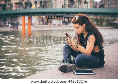 Young beautiful reddish brown hair caucasian girl seated on a sidewalk using a smartphone looking the screen - technology, social network, communication concept - dress with black shirt and blue jeans - stock photo