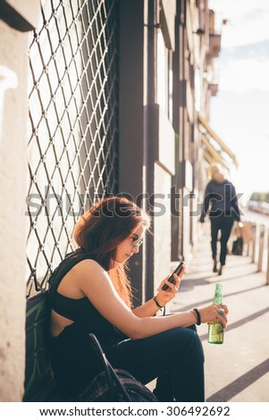 Young beautiful reddish brown hair caucasian woman seated on a sidewalk drinking a beer using smartphone - carefreeness, freshness, youth concept - dressed with black shirt and blue jeans