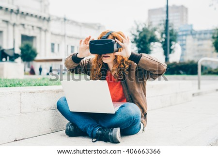 Young beautiful redhead caucasian business woman  sitting with laptop on his knee using 3D viewer - futuristic, multitasking, technology concept