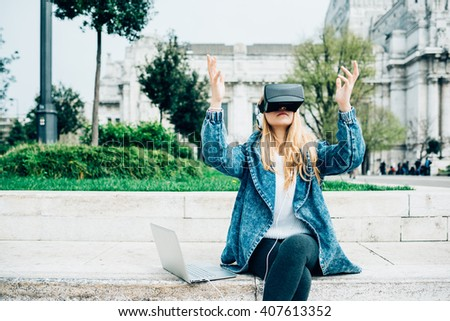 Young beautiful redhead caucasian business woman  sitting with laptop using 3D viewer - futuristic, multitasking, technology concept - stock photo