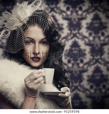 Young beautiful retro lady drinking coffee - stock photo