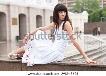 Young beautiful sad woman sits over city theater background