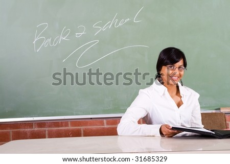 young beautiful school teacher sitting in front of blackboard