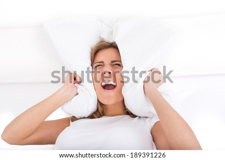 young beautiful screaming woman screaming and covering her ears with pillow because of noise. Noise or insomnia concept