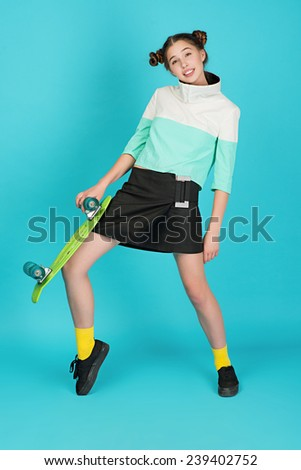 Young beautiful sensual crazy girl posing on a blue background in the studio with Longboard wearing a fashionable outfit, smiling - stock photo