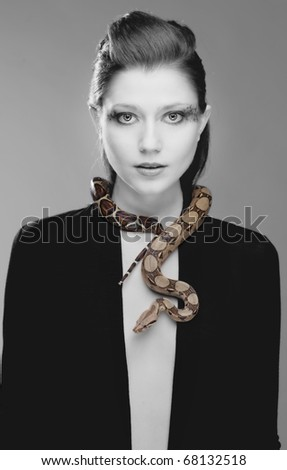 Young, beautiful, sensual woman with snake around her neck; a lot of copyspace available - stock photo