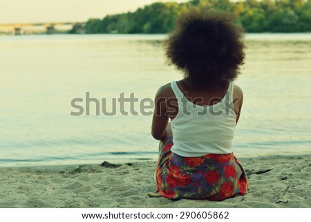 Young beautiful, sexy black girl posing and flirting in the summer park near the old building and water - stock photo