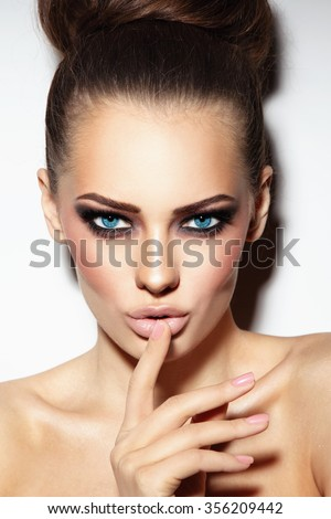 Young beautiful sexy blue-eyed woman with smoky eyes and stylish hair bun - stock photo