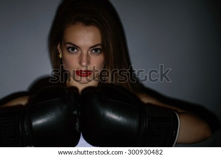 Young beautiful sexy boxer woman over grey background