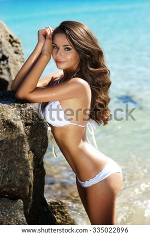 Young beautiful sexy female model standing in blue water near huge rocks. Pretty gorgeous bikini girl posing on a hot summer sunny day - stock photo